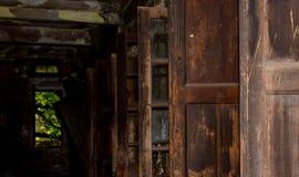 Alte Schadent?ren Fenster in einem dunklen Haus des alten Schadens stockfotos