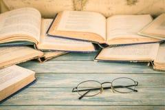 Alte Schauspiele auf gelber Papieroberfläche mit Ausschnittzeichen Brillen unter alten Büchern Lizenzfreies Stockfoto