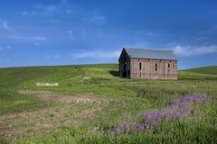 Alte Scheune auf dem grünen Gebiet Stockfotografie