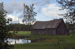 Alte Scheune nahe bei einem Teich im Land in Lettland Lizenzfreie Stockbilder