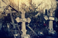 Alte schiefe Grab- Kreuze auf den geworfenen Gräbern am Kirchhof lizenzfreie stockbilder