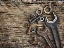 Alte Schlüssel auf den Nüssen - und - Bolzen auf einem hölzernen grungy Hintergrund Stockfotos