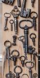 Alte Schlüssel auf hölzerner Wand Stockfotos