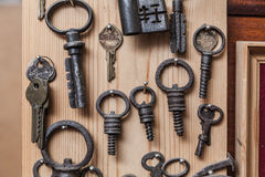 Alte Schlüssel auf hölzerner Wand Stockbilder