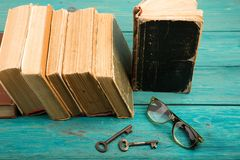 Alte Schlüssel, Gläser und Stapel antike Bücher auf blauem hölzernem Schreibtisch Lizenzfreie Stockfotografie