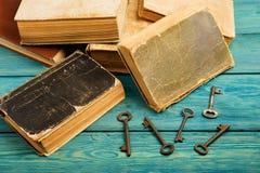 Alte Schlüssel, Stapel antike Bücher auf blauem hölzernem Hintergrund Lizenzfreies Stockbild