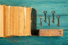 Alte Schlüssel, Stapel antike Bücher auf blauem hölzernem Hintergrund Lizenzfreie Stockbilder
