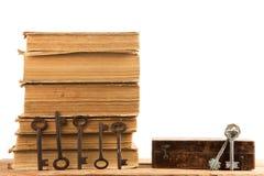 Alte Schlüssel, Stapel antike Bücher lokalisiert auf weißem Hintergrund Lizenzfreie Stockfotos