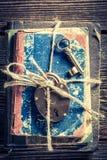 Alte Schlüssel und Bücher auf altem Holztisch Stockfotografie