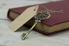 Alte Schlüssel und Buch auf einem rustikalen Hintergrund Stockfotografie