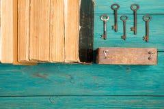 Alte Schlüssel und Stapel antike Bücher auf blauem hölzernem Schreibtisch Lizenzfreie Stockfotografie