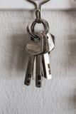 Alte Schlüsselweinlese, die an der Zementwand hängt Stockbild