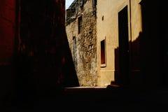 Alte schmale Straße von den Schatten stockbild