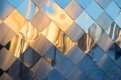 Alte, schmutzige Aluminiummetallwand-Fassadenplatte mit der Raute, ähnlich den Skalen und den Fliesen Reflexion des Sonnenunterga Lizenzfreie Stockfotografie