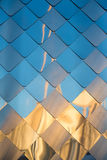 Alte, schmutzige Aluminiummetallwand-Fassadenplatte mit der Raute, ähnlich den Skalen und den Fliesen Reflexion des Sonnenunterga Stockbild