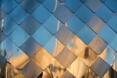 Alte, schmutzige Aluminiummetallwand-Fassadenplatte mit der Raute, ähnlich den Skalen und den Fliesen Reflexion des Sonnenunterga Stockfoto