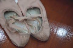 Alte schmutzige Ballettschuhe auf hölzernem Hintergrund | Ballerina benutzte Schuhe Stockbild