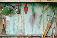 Alte schmutzige Bauernhofgartenarbeitwerkzeuge, Spaten, Gabel und Rührstange auf hölzerner Wand Lizenzfreie Stockbilder