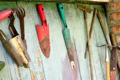 Alte schmutzige Bauernhofgartenarbeitwerkzeuge, Spaten, Gabel und Rührstange auf hölzerner Wand Stockfotos