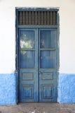 Alte schmutzige blaue Holztür in der Wand des Steinhauses auf Peloponnes Stockfotografie