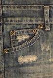 Alte schmutzige Blue Jeans mit Löchern und Kratzen Jeanstasche mit Bronzeknöpfen Niete mit Zeichen JEANS in der Kante Stockfotografie