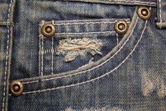 Alte schmutzige Blue Jeans mit Löchern und Kratzen Jeanstasche mit Bronzeknöpfen Niete mit Zeichen JEANS in der Kante Lizenzfreie Stockbilder