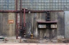 Alte schmutzige Fabrikwand mit Rohren und Stromzentrale Stockfotos