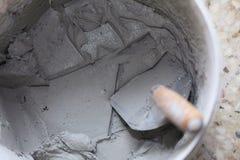 Alte schmutzige Kelle und Eimer auf Baustelle Stockfotos