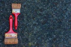 Alte schmutzige Rotbürsten auf Steinhintergrund Lizenzfreies Stockbild