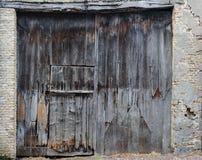 Alte, schmutzige und verwitterte geschlossene hölzerne Scheunentür Stockfotografie