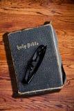 Alte schroffe heilige Bibel auf hölzernem Beschaffenheits-Hintergrund Stockfotografie