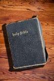 Alte schroffe heilige Bibel auf hölzernem Beschaffenheits-Hintergrund Stockfotos