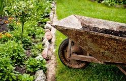 Alte Schubkarre auf Gras Stockfotos