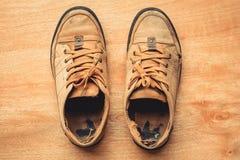 Alte Schuhe auf hölzernem Hintergrund Stockbild