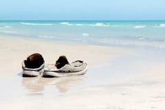Alte Schuhe auf Strand Lizenzfreies Stockfoto