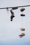 Alte Schuhe, die am Draht - Lebenänderung hängen Stockfotografie