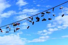 Alte Schuhe, die am elektrischen Draht gegen einen blauen Himmel hängen Stockfotografie