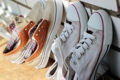 Alte Schuhe, die gegen die Wand in den Schatten trocknen Lizenzfreie Stockfotografie