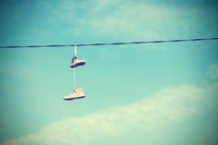 Alte Schuhe Instagram-Retrostils, die an der elektrischen Leitung hängen Lizenzfreie Stockfotografie