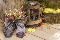 Alte Schuhe mit Blumen auf altem hölzernem Hintergrund Stockfoto