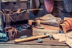 Alte Schusterwerkstatt mit Bürste und Schuhen Stockbild