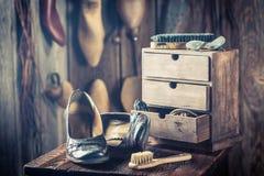 Alte Schusterwerkstatt mit Schuhen und Bürste Stockbilder