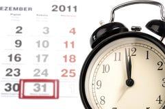 Alte schwarze Alarmuhr mit Kalender Stockfotos