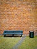 Bank und Backsteinmauer Stockfotografie