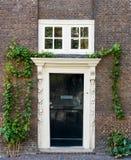 Alte schwarze Holztür mit weißem Rahmen auf brauner Backsteinmauer stockfoto