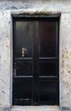 Alte schwarze Tür mit Bronzezuggriff Lizenzfreie Stockbilder