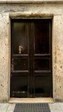 Alte schwarze Tür mit Bronzezuggriff Lizenzfreies Stockfoto