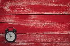 Alte schwarze Uhr auf hölzernem rotem Hintergrund Lizenzfreie Stockfotografie