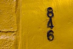 alte schwarze Zahlen in einer gelben Wand Stockfotografie