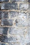 Alte Schwarzweiss-Backsteinmauer als Hintergrund mit rauer Beschaffenheit Lizenzfreies Stockbild